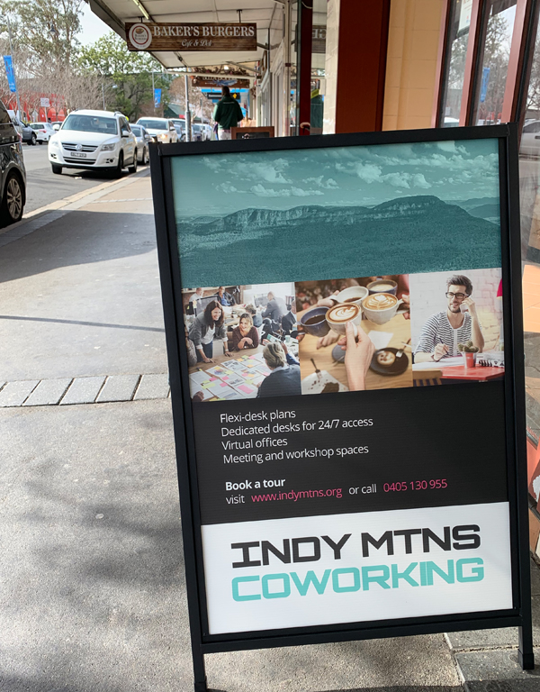 A frame advertising INDY MTNS on pavement in Springwood